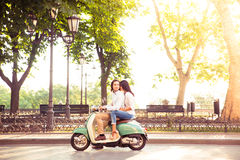Trendy couple riding a scooter in the mornin Royalty Free Stock Image
