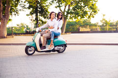 Trendy couple riding a scooter Stock Images