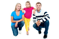 Trendy couple squatting with girl child in between. Studio shot Stock Image