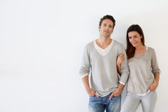 Trendy couple standing on white wall Royalty Free Stock Photography
