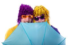 Trendy couple with sunglasses and wigs protected by an umbrella Stock Photos