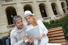 Trendy couple using tablet sitting on public bench royalty free stock image