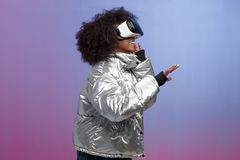 Trendy curly brown-haired girl dressed in a silver-colored jacket uses the virtual reality glasses in the studio on neon. Background stock photography