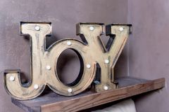 Trendy decorative wooden inscription Joy. Lovely word. Jnjoy concept. Fashion nightlight, night lamp.sign with bronze Royalty Free Stock Images