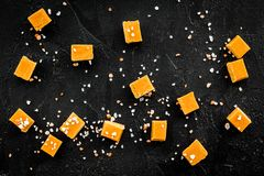 Trendy dessert. Salted caramel. Caramel cubes sprinkled by salt crystals on black background top view Royalty Free Stock Photo
