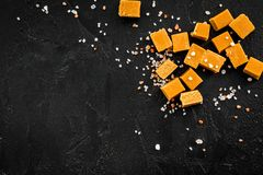 Trendy dessert. Salted caramel. Caramel cubes sprinkled by salt crystals on black background top view copy space Stock Photos