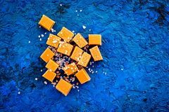 Trendy dessert. Salted caramel. Caramel cubes sprinkled by salt crystals on blue background top view copy space Stock Photos