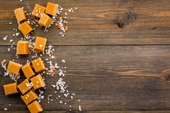 Trendy dessert. Salted caramel. Caramel cubes sprinkled by salt crystals on dark wooden background top view space for Stock Images
