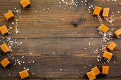 Trendy dessert. Salted caramel. Caramel cubes sprinkled by salt crystals on dark wooden background top view space for Royalty Free Stock Photos
