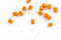 Trendy dessert. Salted caramel. Caramel cubes sprinkled by salt crystals on white background top view space for text Stock Photos