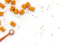 Trendy dessert. Salted caramel. Caramel cubes sprinkled by salt crystals on white background top view space for text Royalty Free Stock Photos
