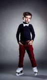 Trendy dressed boy posing ice skating in studio Royalty Free Stock Photo