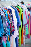 Trendy dresses with colorful floral prints. Close-up of summer trendy dresses with colorful floral prints, exposed on hangers in an outlet shop Royalty Free Stock Photo