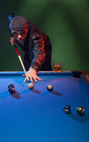 Trendy dude playing a game of pool in a nightclub Stock Photos