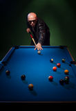 Trendy dude playing a game of pool in a nightclub Royalty Free Stock Images