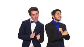 Trendy elegant young guys dancing - studio shot. Trendy elegant young guys dancing a white background stock video footage