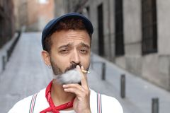 Trendy ethnic man smoking a joint outdoors royalty free stock image