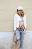 Trendy and fancy blond woman in ripped jeans. Trendy woman leaning on city wall Stock Image