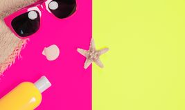 Trendy fashion beach accessories on a bright colorful background. Sunglasses, fragment of a straw hat, a bottle of sunscreen. Lotion, dried starfish and shells royalty free stock photo
