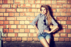 Trendy Fashion Girl at the Brick Wall Royalty Free Stock Image