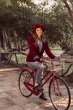 Trendy fashion girl riding bike on fall season Royalty Free Stock Images