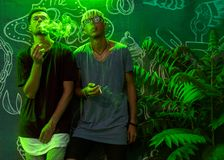 Trendy fashion guys smoking in neon green light royalty free stock photo