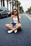Trendy fashion model posing with skate board wearing colorful sunglasses Royalty Free Stock Photos