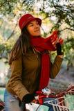 Trendy fashion woman riding bike on fall season Stock Images
