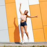 Trendy fashionable girl emotionally jumping Royalty Free Stock Photography