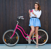 Trendy Fashionable Girl with Vintage Bike on Wooden Background. Pink vintage camera in her hand. Toned Photo. Modern Youth Lifesty Stock Photos