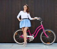 Trendy Fashionable Girl with Vintage Bike on Wooden Background. Toned Photo. Modern Youth Lifestyle Concept. Trendy Fashionable Sexy Girl with Vintage Bike on Stock Photography
