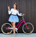 Trendy Fashionable Girl with Vintage Pink Bike on Black Wooden Background. Shows sign Victory. Toned Photo. Modern Youth Lifestyle Royalty Free Stock Images