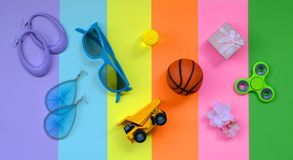 Trendy fashionable pastel composition with earrings, sunglasses, beverage can, basketball ball, toy truck, gift box, flower and. Spinner on pink, violet, green stock image