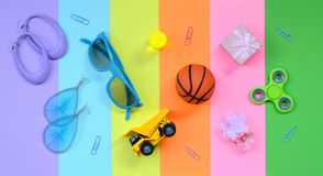Trendy fashionable pastel composition with earrings, sunglasses, beverage can, basketball ball, toy truck, gift box, flower and. Spinner on pink, violet, green stock photo