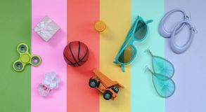 Trendy composition with earrings, sunglasses, beverage can, basketball ball, toy truck, gift box, flower and spinner. Trendy fashionable pastel composition with royalty free stock photography