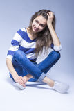 Trendy and Fashionable Positive Caucasian Brunette Girl Sitting on Floor With Crossed Legs stock images