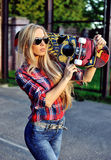 Trendy fashionable young woman with skateboard outdoor Stock Photography