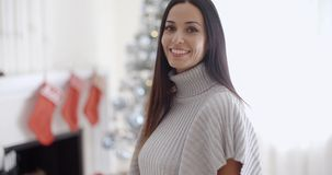 Trendy fashionable young woman. Wearing a winter polo neck posing in her living room at Christmas giving the camera a lovely warm friendly smile stock footage