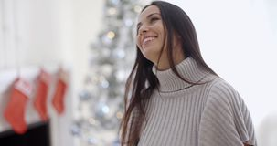 Trendy fashionable young woman. Wearing a winter polo neck posing in her living room at Christmas giving the camera a lovely warm friendly smile stock video footage