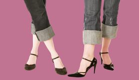Trendy feet with blue jeans and leather shoes. Legs of two women -showing off leather shoes - clipping path incl Stock Photos