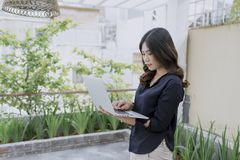 Trendy female business woman standing with laptop  in terrace outdoor. Student girl reading a presentation on laptop. education, royalty free stock photo