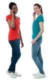 Trendy females speaking over cellphone Stock Images
