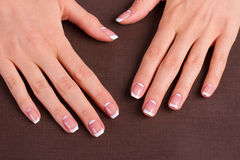 Trendy french manicure. Trendy french manicure on a brown background royalty free stock image