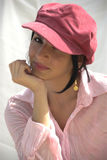 Trendy Girl. A fashion conscious woman looking from beneath her hat Stock Photography