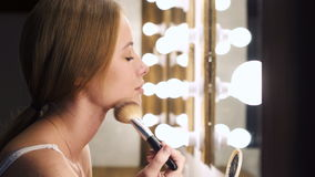 Trendy girl applying cosmetic with big brush. Urban girl looking in mirror and applying cosmetic with brush having smile before meeting in room. Professional stock footage