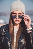 Trendy girl with attitude holding sunglasses Royalty Free Stock Photography
