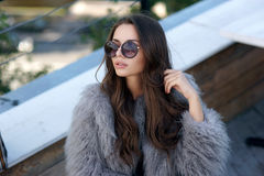 Trendy girl in fur coat Stock Photos