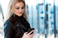 Trendy girl in the hat, outdoor. Young woman uses phone. Portrait on background of modern buildings Stock Photography