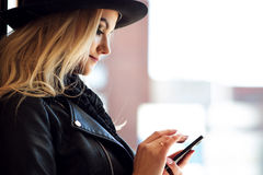 Trendy girl in the hat, outdoor. Young woman uses phone. Portrait in profile Royalty Free Stock Images