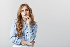 Trendy girl having doubts about new dress. Studio shot of disbelieving good-looking female student in blue-collar shirt. Touching lip and staring with Stock Image